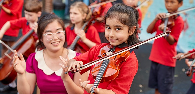 A primary school girl plays the violin while her teacher watches.